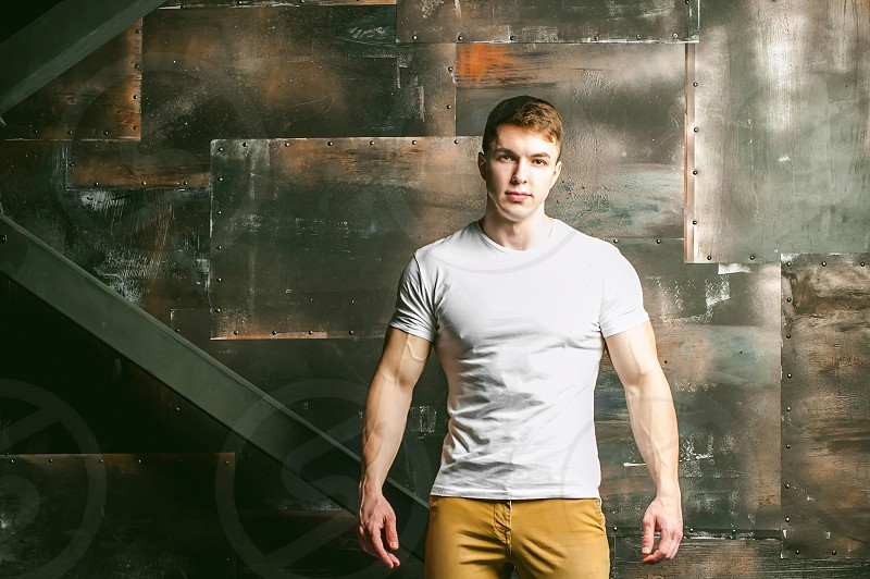 Young sexy men bodybuilder athlete Studio portrait in a loft on the background of a stylized metal wall a guy model in a white T-shirt and brown trousers photo