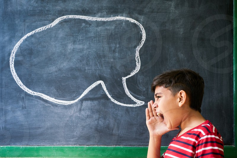 Concept on blackboard at school. Young people student and pupil in classroom. Hispanic boy screaming in class with drawing of cloud on blackboard. Portrait of frustrated male child photo