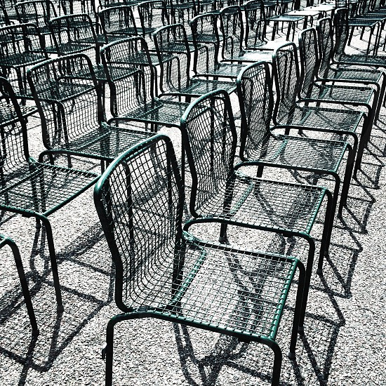 Green wire chairs lined up in rows in outdoor setting photo