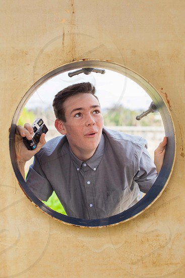 boy in hole holding a cemera photo