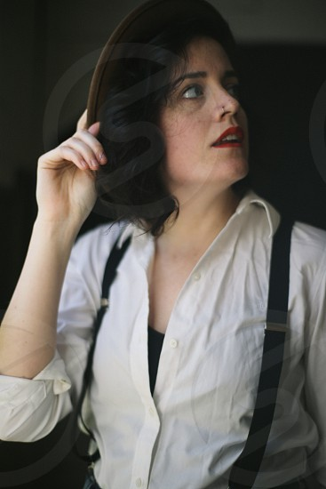 woman with black hair wearing brown hat white buttoned down shirt and black over alls photo