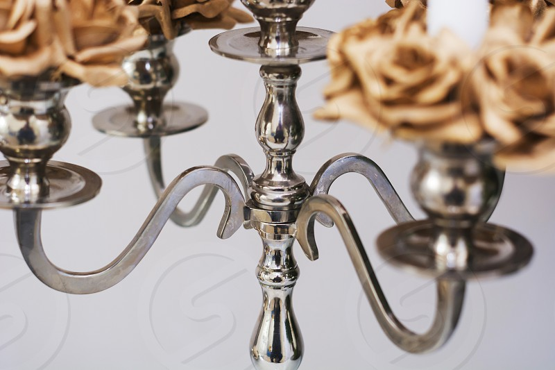 close up of a silver candelabrum with blurred golden roses  photo