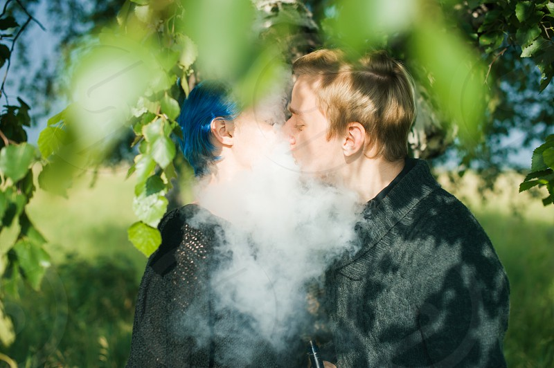 young couple with dyed hair smoking electronic cigarettes near birches. cloud head. cloud chasing. vaping photo