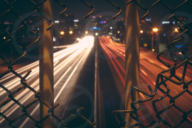 Long exposure freeway city light breaking through the fence. Streaking lights. Break in a chain link fence looking at downtown San Diego.  photo