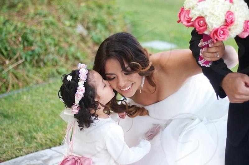 little girl kissing the bride photo