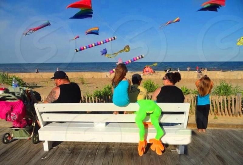 Family summer beach flying kites kids wonder bench stuffed animal ocean sand board walk  photo