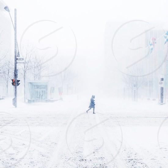 woman wearing black coat walking on snow road photo
