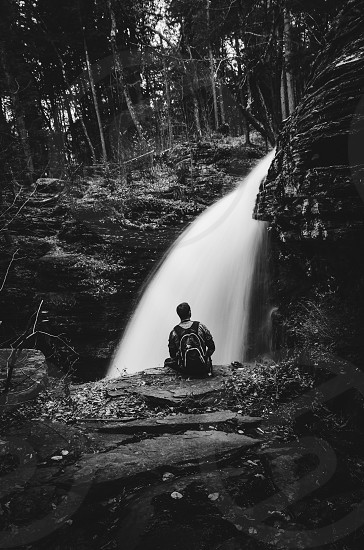 grayscale photo of man sitting in cliff facing water fall photo