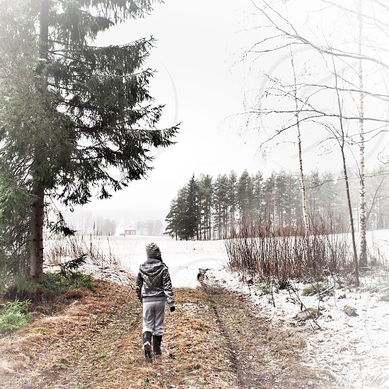 person wearing gray hoodie jacket with gray bottoms and black galoshes walking on brown grass near trees coated with snow during daytime photo