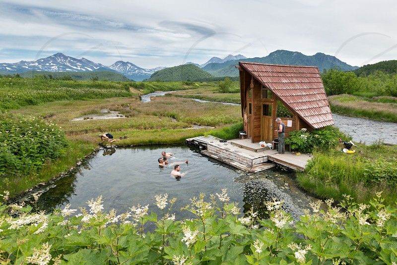NALYCHEVO KAMCHATKA PENINSULA RUSSIA - JULY 11 2014: Goryacherechensky group hot springs in nature park Nalychevo people swimming in the natural thermal pools. Kamchatka Far East Russia. photo