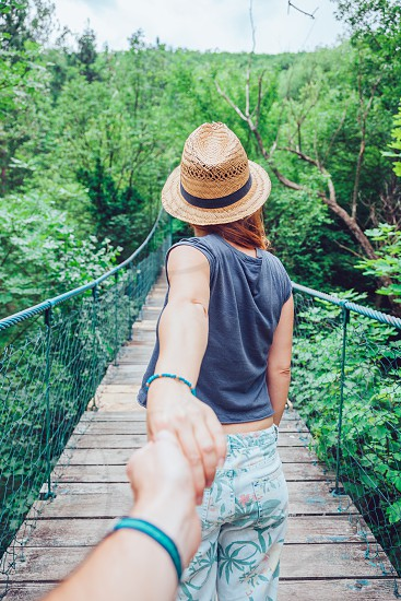 Young woman holding hand on the bridge leading to adventure photo