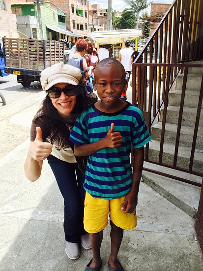 street photography of female and boy doing thumbs up hand gestures photo