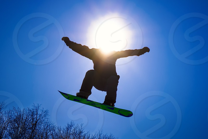 Snowboard rider jumping on blue sky background and sun shining in place of his head photo