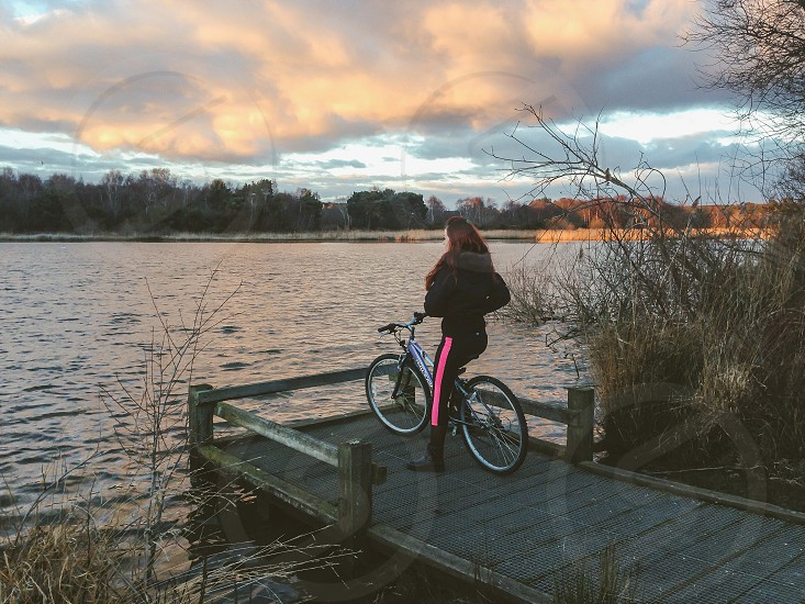 Enjoying the sunset female cyclist water nature ripples lake winter bike ride photo