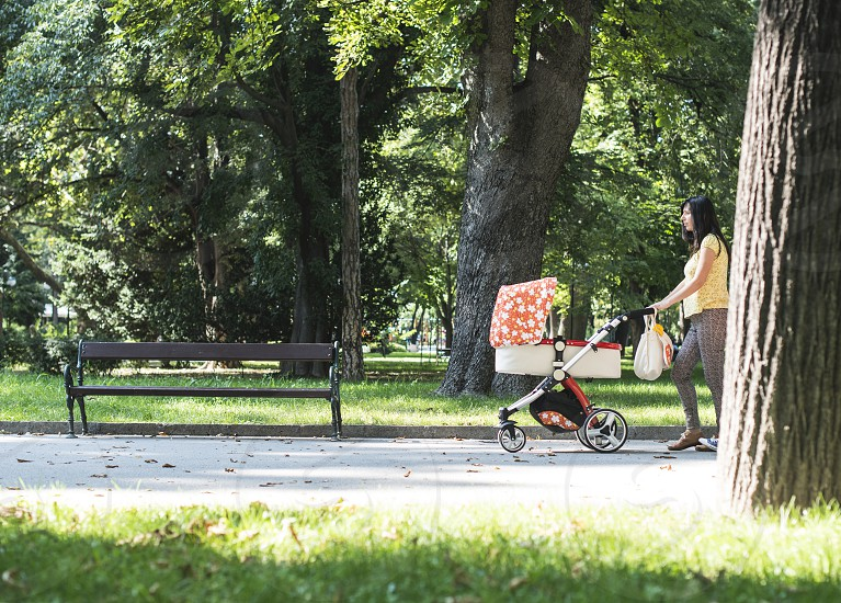 Mother walking in the park with baby buggy. Sunny day photo