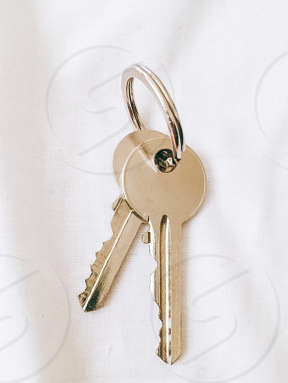chrome twin keys on stainless key rack on top of white surface photo