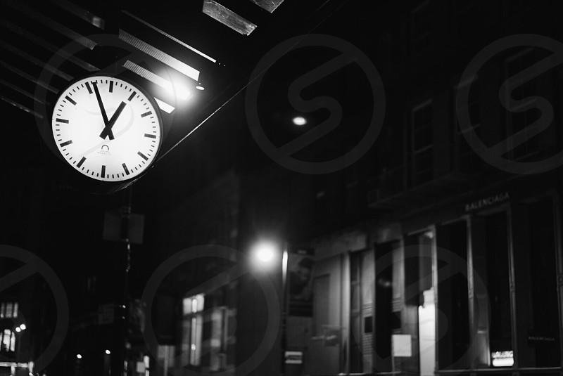 illuminated clock near buildings in black and white photo