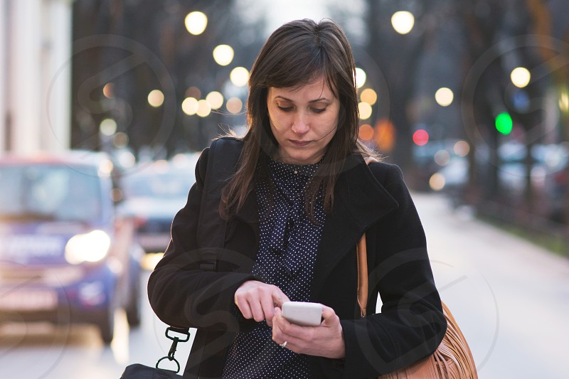 Woman browsing on her mobile phone in the city center photo