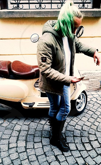 woman with blond and green hair using phone on the street in German city Tubingen photo