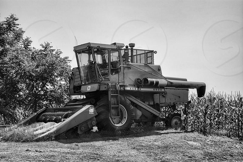 John Deere combine waiting for fall harvest. Black & white.   photo