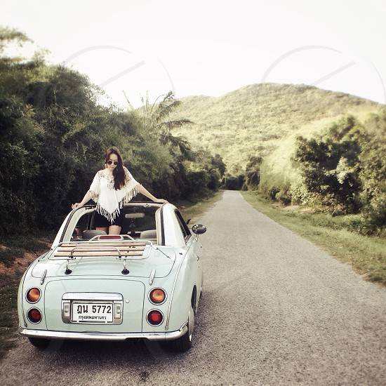 woman in white fringe poncho standing in mint convertible vintage car on desolate road photo