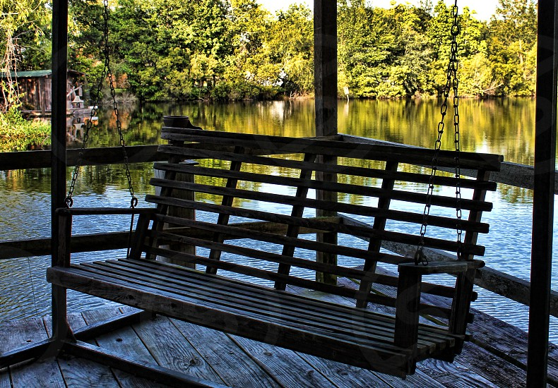 A wooden bench swing is seen in silhouette as it hangs on a porch of a country home near a pond or lake surrounded by trees. photo