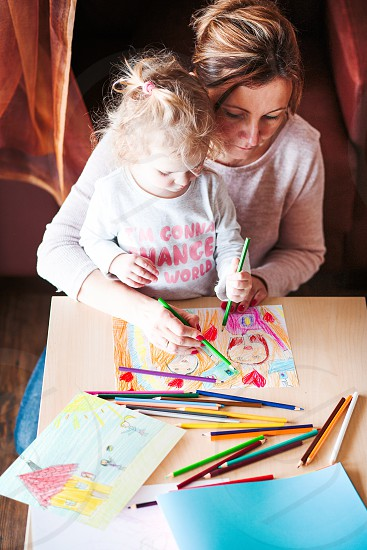 Mom with little daughter drawing a colorful pictures of family using pencil crayons sitting at table indoors. Shot from above photo