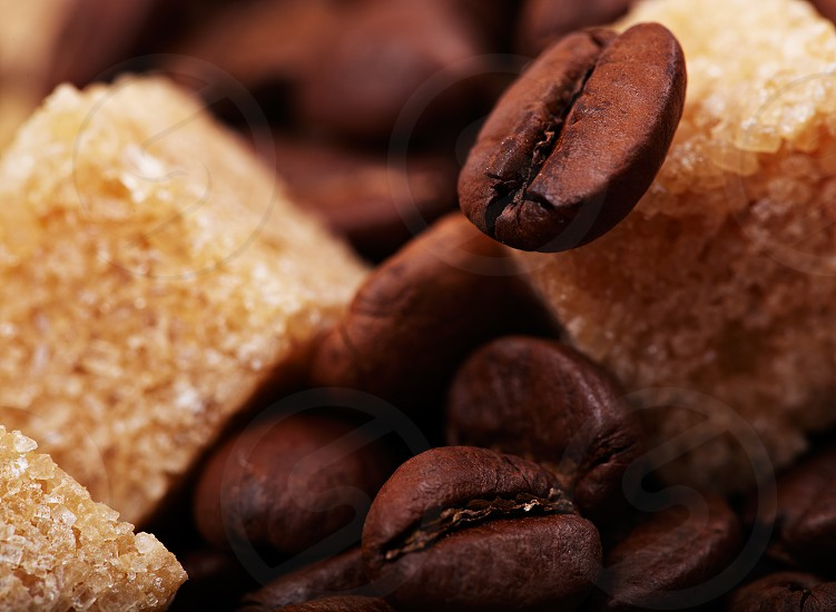 Beautiful coffee beans background with brown sugar cubes. Natural morning sunlight. photo