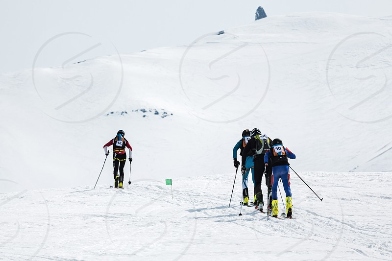 AVACHA KORYAK VOLCANOES KAMCHATKA RUSSIA - APRIL 27 2014: Two teams of ski mountaineers climb the volcano on skis. Team Race ski mountaineering Asian ISMF Russian Kamchatka Championship. photo