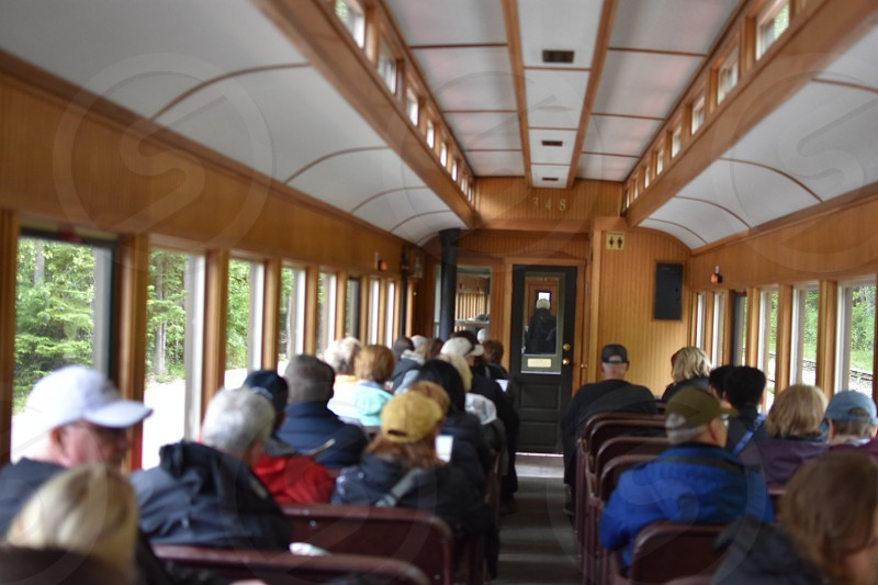 A train car filled with people travel through the forest of the Rocky Mountains photo