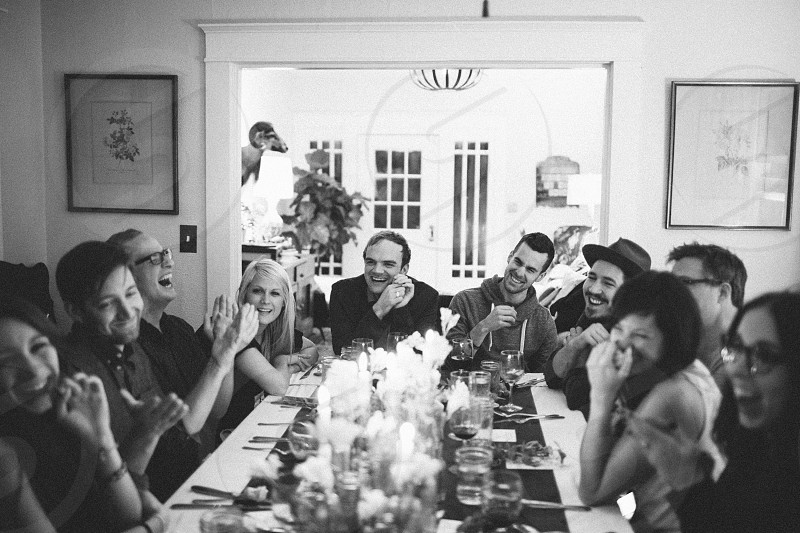 men and women laughing near dining table photo