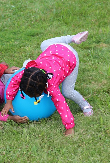 Child in pink jacket  playing with ball photo