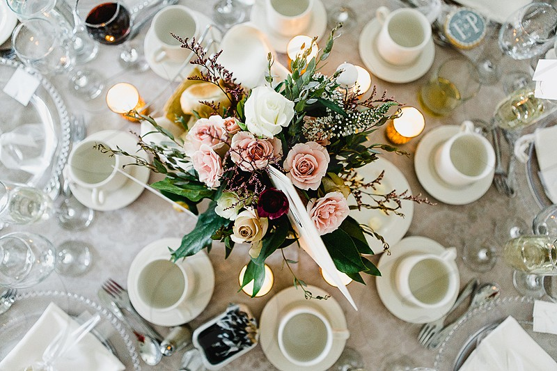A romantic table setting with pink roses and greenery photo