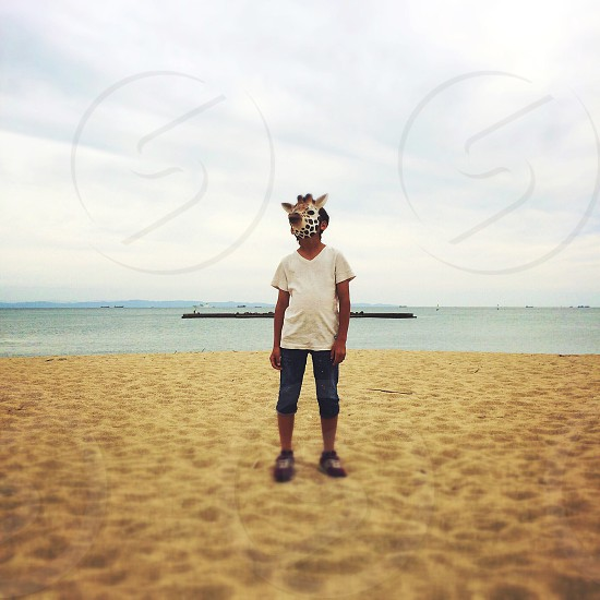 boy in giraffe mask and white shirt on beach photo