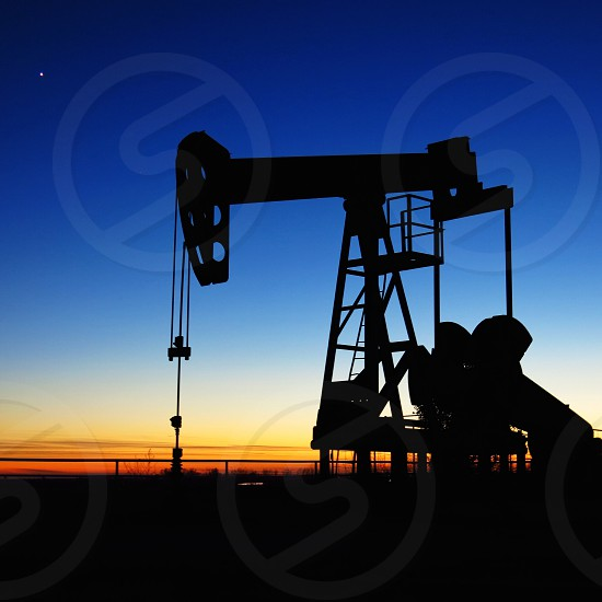 An oil pump in an Oklahoma pasture sits idle at dusk. photo