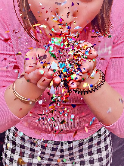 Confetti celebrate celebrating party blowing throwing colorful bright sparkles millennial young woman girl pink fashionable fashion close up partying fun having fun lifestyle glitter multi colored happy bright and colorful natural light photo