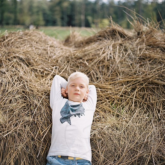 Boy dreaming in a haystack photo