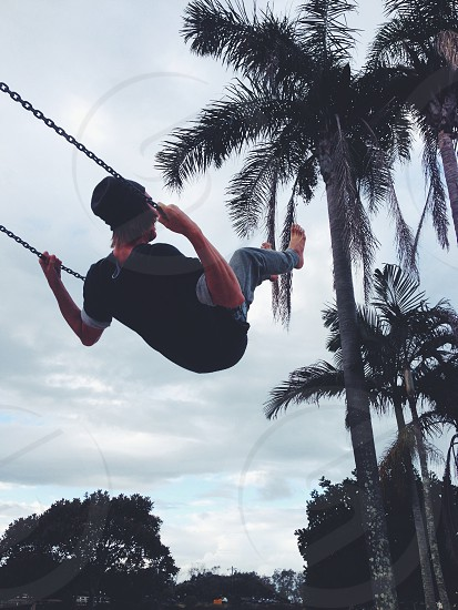 man in black t shirt on swing photo