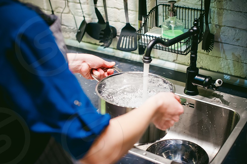 woman housewife in the kitchen. girl collects water from the tap in the pan photo
