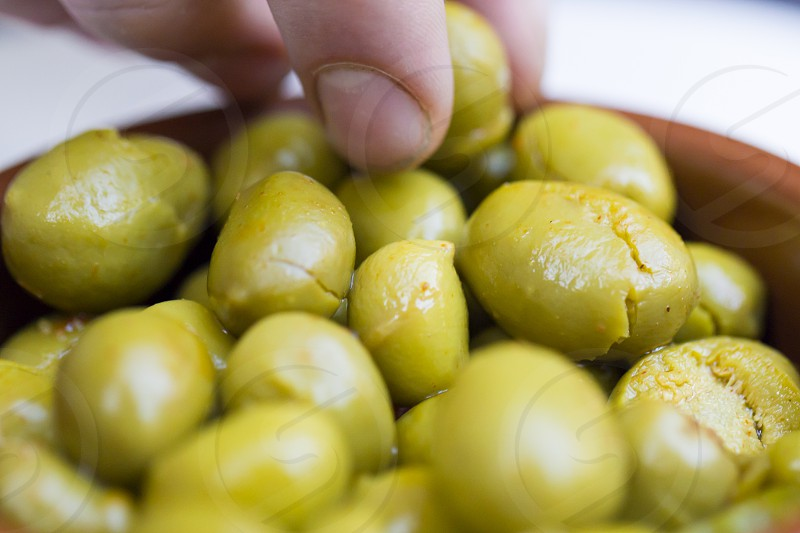 A man takes pickled olive from a saucer with his fingers. photo