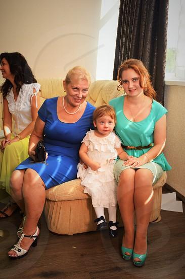 3 women sitting on beige sofa beside girl in white ruffled dress smiling photo