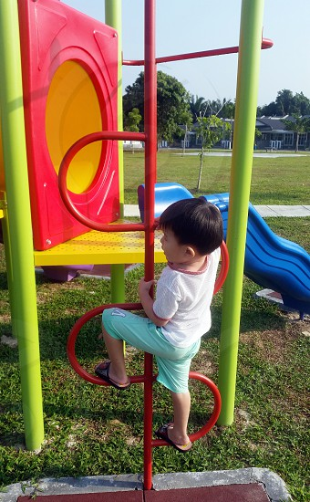 boy wearing white shirt and teal shorts climbing red pole outdoor playground during daytime photo