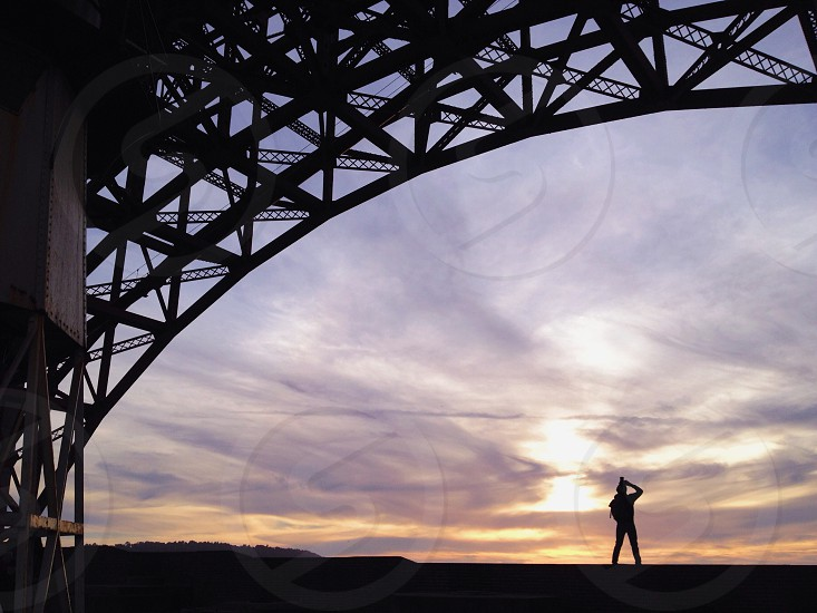person standing below bridge with sunset view photo