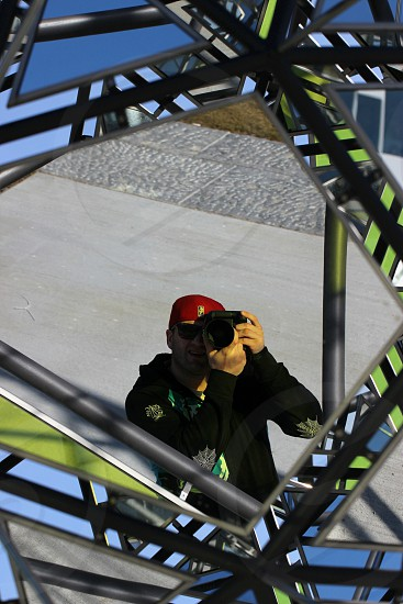 man in black jacket holding black camera photo