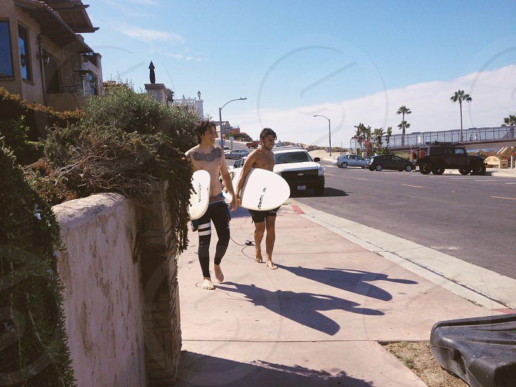 2 man carrying surf board walking on street photography photo