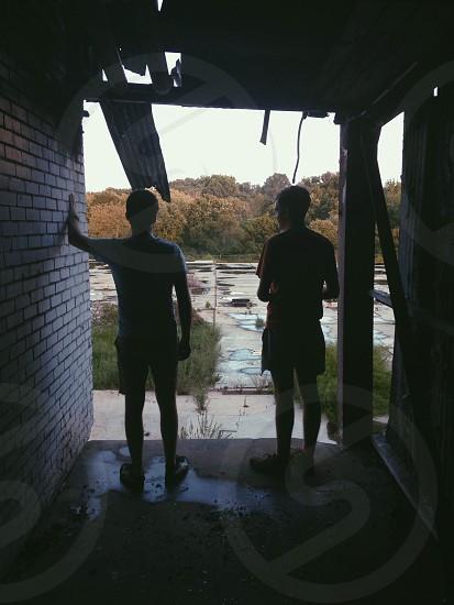 two men standing near brick wall photo