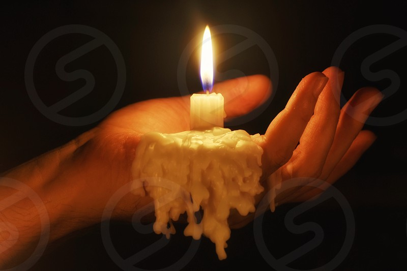 person holding candle stick while melting photo