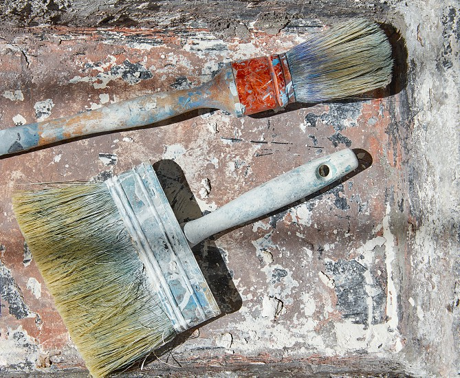 Paint brushes used on grunge bucket in improvement background photo