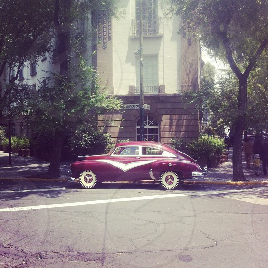 red vintage car near building photo