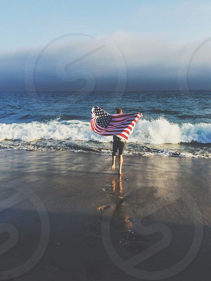 person holding the american flag by the sea shore photo